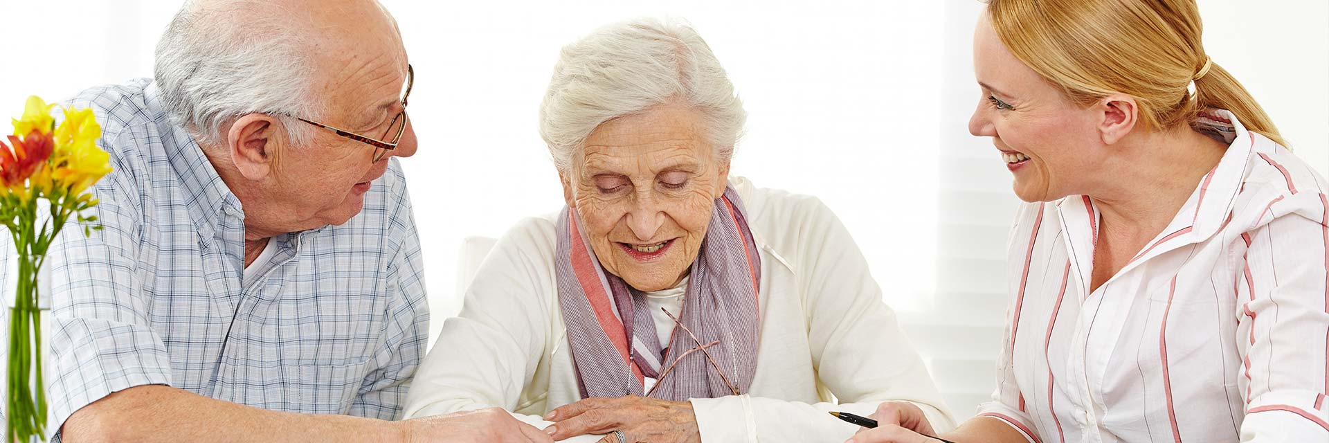 Ein älteres Paar unterhält sich mit einer freundlichen Pflegekraft