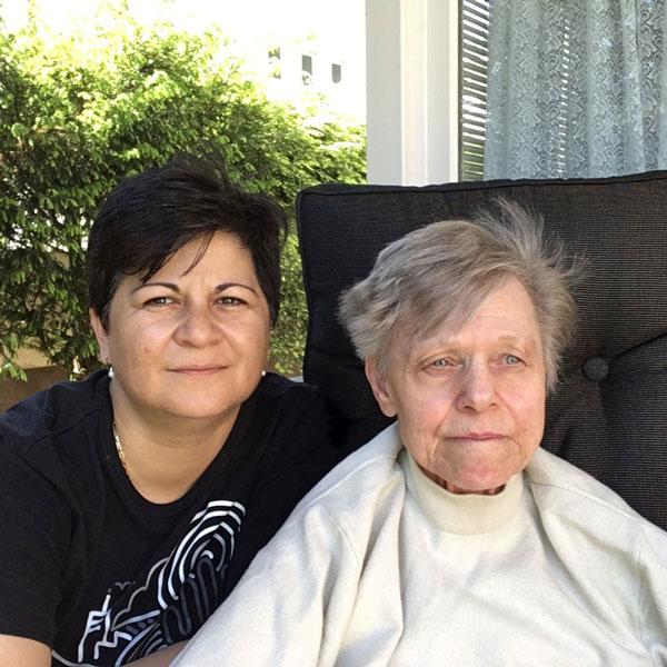 Eine Frau mittleren Alters und ihre pflegebedürftige Verwandte lächeln in die Kamera