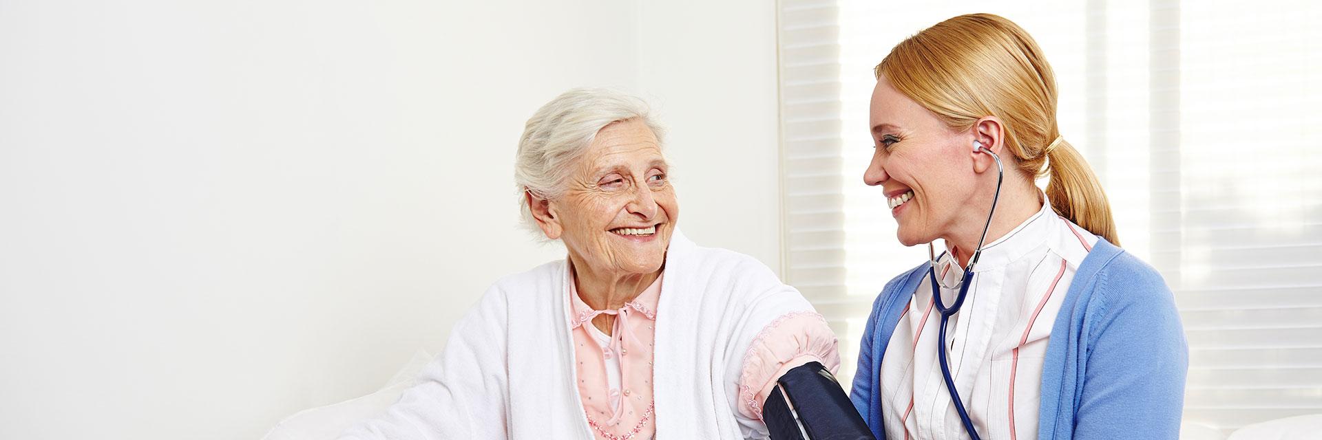 Eine Altenpflegerin misst einer alten Dame mit Hilfe eines Blutdruckmessgeräts den Blutdruck