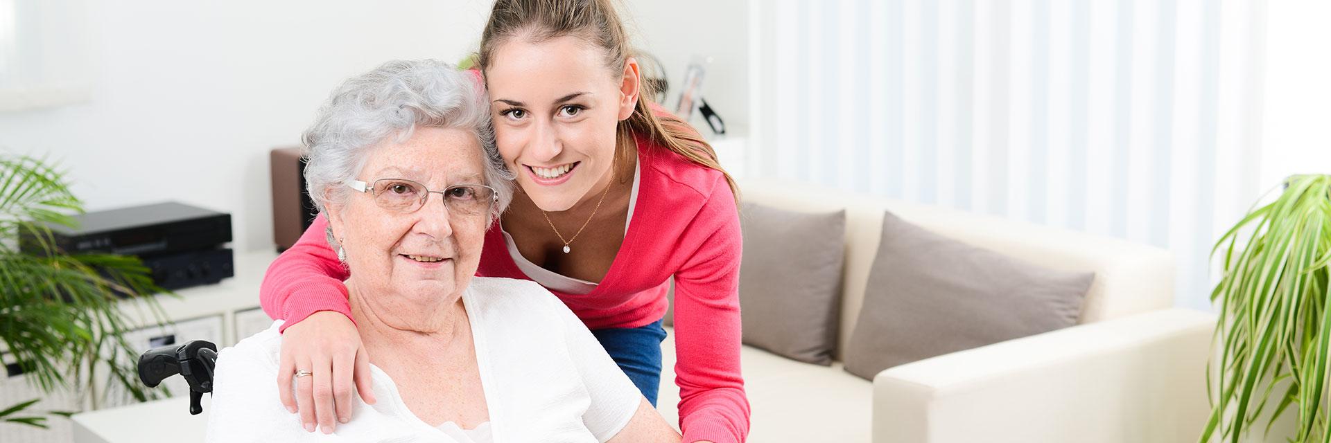 Pflegerin des ambulanten Pflegedienstes umarmt eine alte Dame