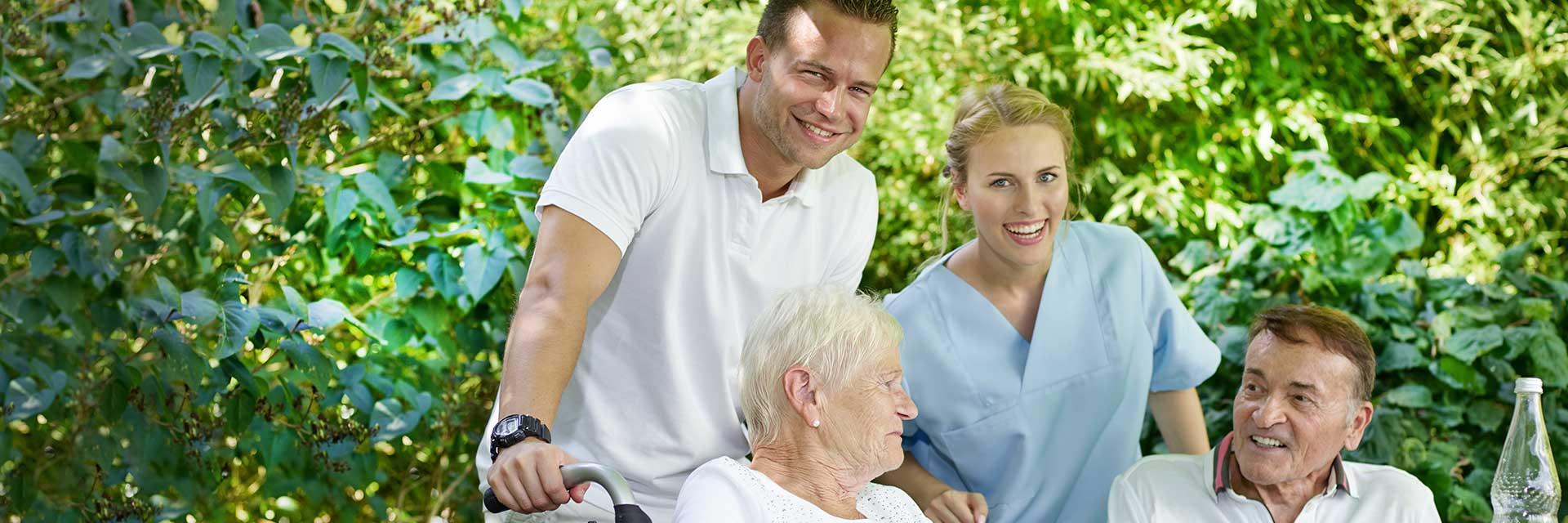 Ein männlicher und eine weibliche Pflegerin lachen in die Kamera, während sie zwei pflegebedürftige Senioren im Rollstuhl vor sich schieben