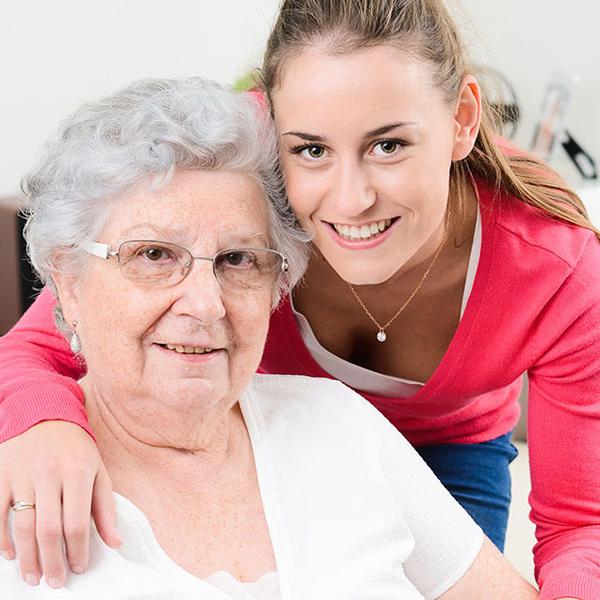 Eine Pflegerin und ein älterer, pflegebedürftiger Herr, posieren für ein Foto